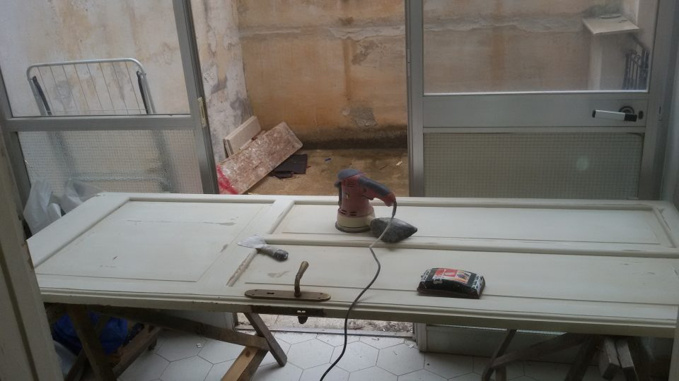 Levigare la porta utilizzando una levigatrice elettrica per garantire una superficie liscia
